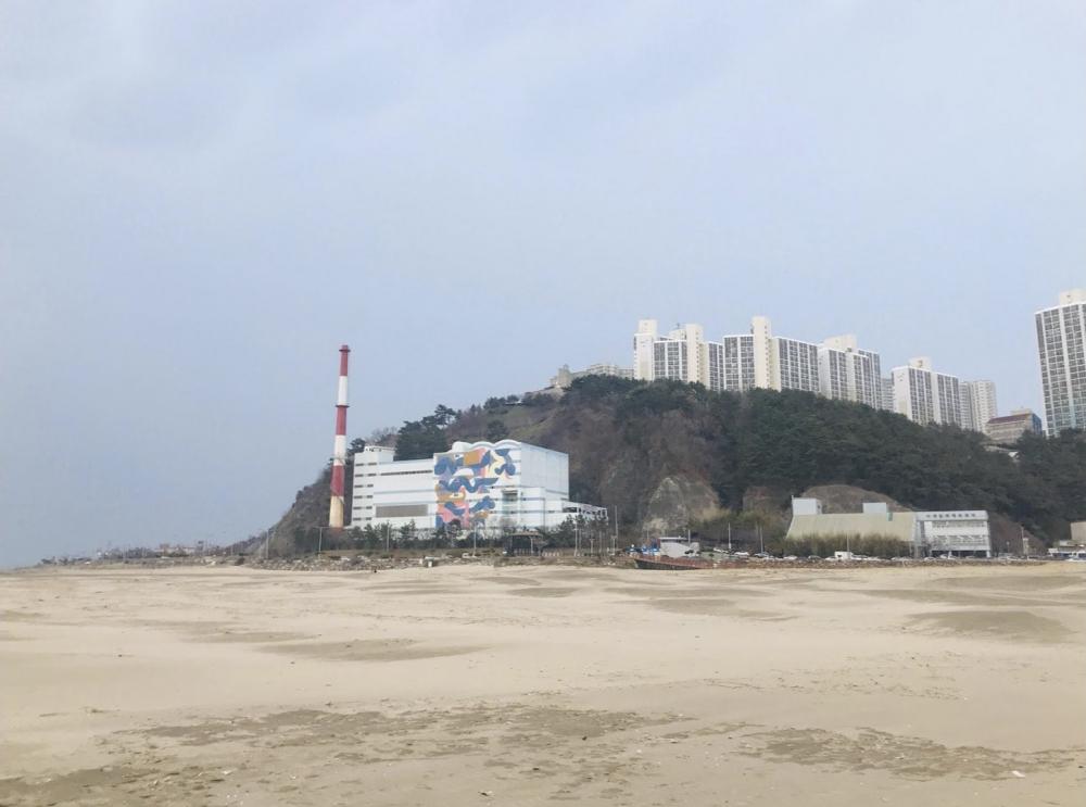 부산 다대포 해안에서 바라본 과거 김복동의 가게가 있던 자리에는 높은 굴뚝의 다대환경사업소가 들어서 있다. (사진 제공 : 송원근)