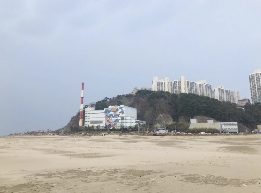 부산 다대포 해안에서 바라본 과거 김복동의 가게가 있던 자리에는 높은 굴뚝의 다대환경사업소가 들어서 있다. (사진 제공: 송원근)