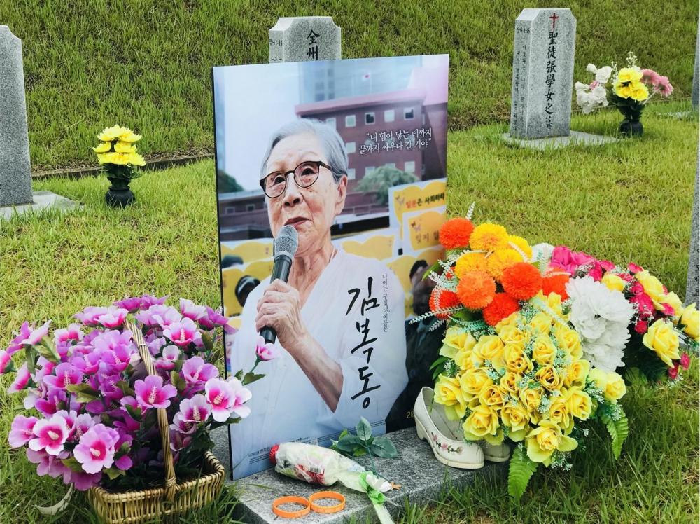 영화가 완성되고, 영화 포스터를 들고, 천안 망향의 동산에 있는 김복동의 묘역을 찾았다. (사진 제공: 송원근)
