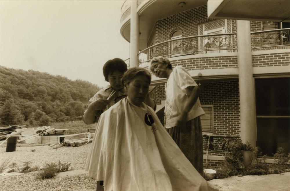 김복동이 나눔의집 야외에서 머리를 다듬고 있다. 오른쪽은 김순덕.  (사진 제공 : 나눔의 집)